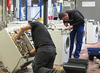 Réparation d'un lave-linge dans un magasin d'économie sociale